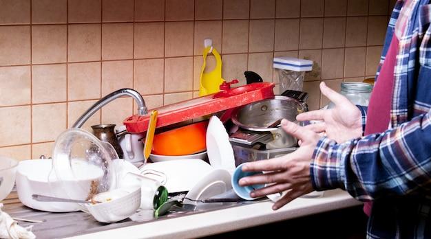 Schockierter handkerl nahe vielen schmutzigen tellern, die in der wanne in der küche liegen, die sie waschen möchten Premium Fotos