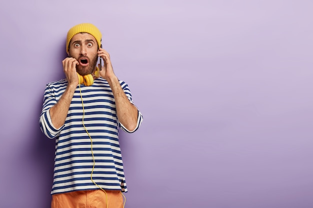 Schockierter junger mann bestellt per handy, fassungslos kann er keinen tisch im restaurant reservieren, sieht mit omg ausdruck aus, trägt modisches outfit Kostenlose Fotos
