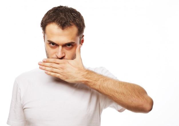 Schockierter junger mann, der mund mit händen bedeckt Premium Fotos