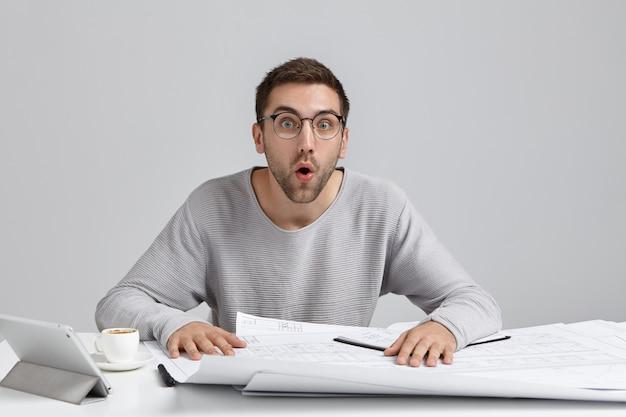 Schockierter männlicher ingenieur entwickelt neues bilddesign, sieht mit offenem mund aus und erinnert sich an wichtige treffen Kostenlose Fotos