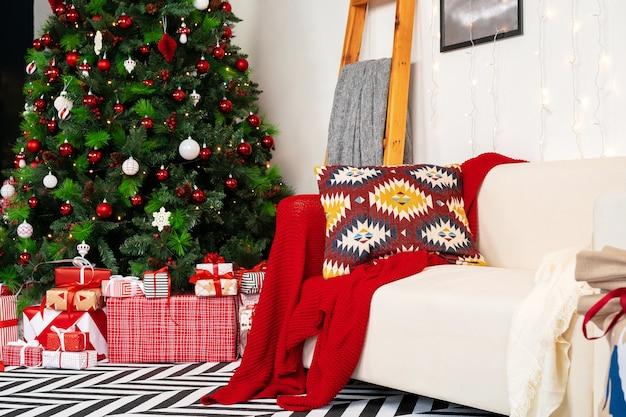Schön verzierter weihnachtsraum mit tannenbaum und weißem sofa Premium Fotos
