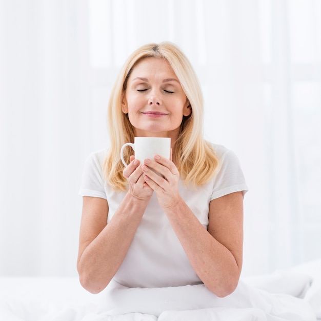 Schöne ältere frau, die einen tasse kaffee genießt