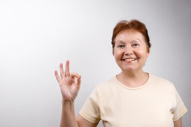 Schöne ältere frau zeigt okay auf weiß in einem hellen t