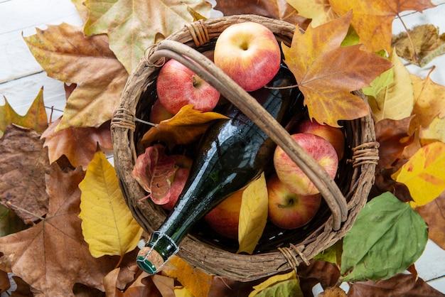 Schöne äpfel und eine flasche apfelwein, auf herbstlaub Premium Fotos