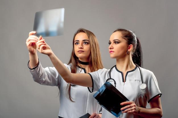 Schöne ärztinnen, die medizinische mäntel mit den stethoskopen betrachten röntgenstrahl und besprechen die ergebnisse tragen. Premium Fotos