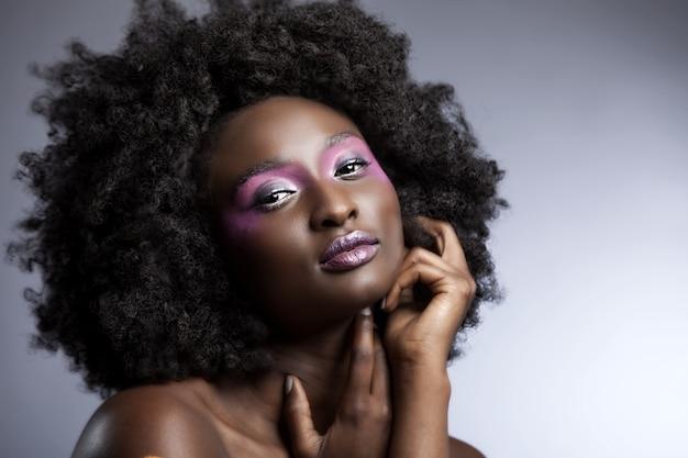 Schöne afrikanerin mit großem lockigem afro und blumen im haar Kostenlose Fotos