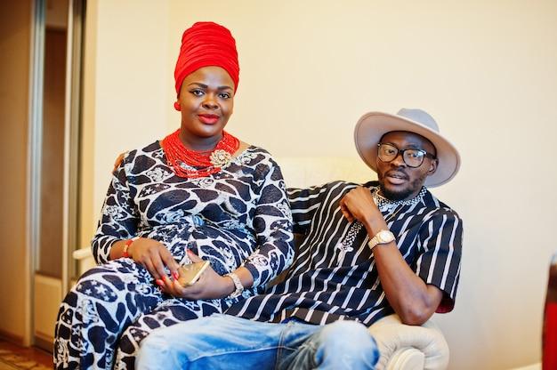 Schöne afroamerikanerfrau im trachtenkleid und im hübschen sitzen und im lächeln des schwarzen mannes. Premium Fotos