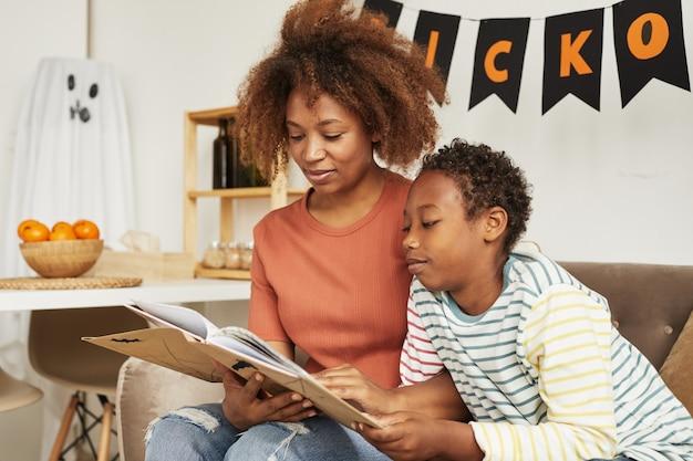Schöne afroamerikanische frau, die auf sofa im wohnzimmer mit ihrem jugendlichen sohn sitzt, der interessantes halloween-geschichtenbuch liest Premium Fotos