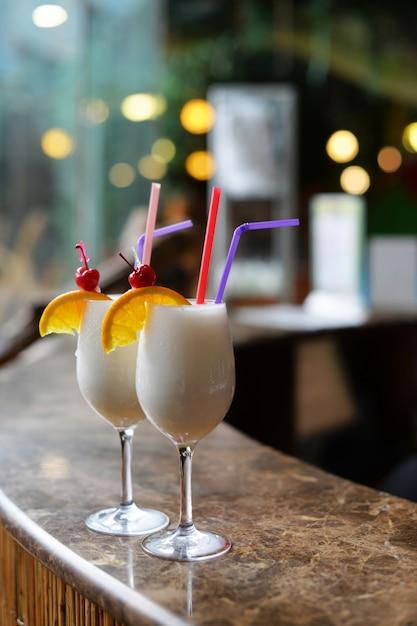 Schöne alkoholische cocktails mit ananas-pinacolada und kokosnuss auf der theke Premium Fotos