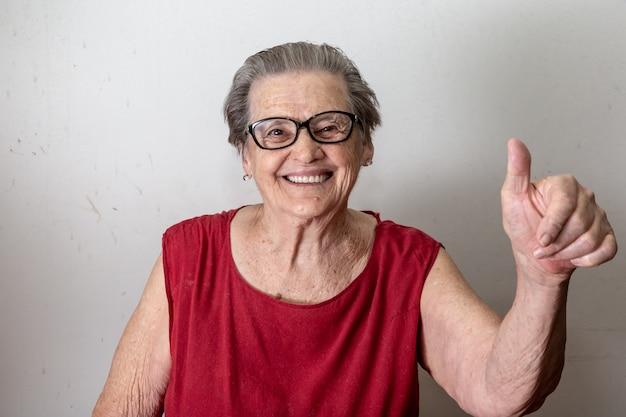Schöne alte frau mit zwei stößen. netter kaukasischer senior, der zwei daumen oben auf weißem hintergrund zeigt. Premium Fotos