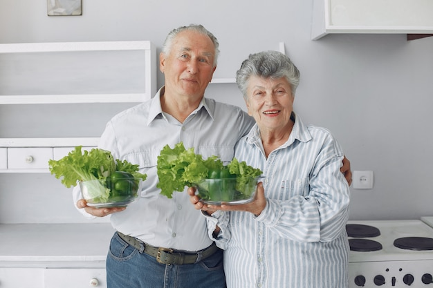 Schöne alte paare bereiten lebensmittel in einer küche zu Kostenlose Fotos