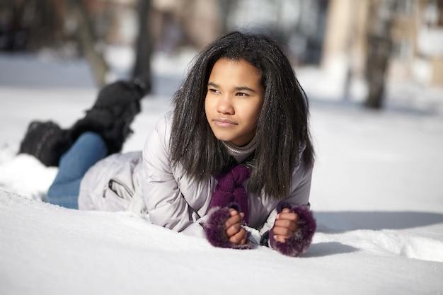Schöne amerikanische schwarze frau, die draußen im schnee liegt Kostenlose Fotos