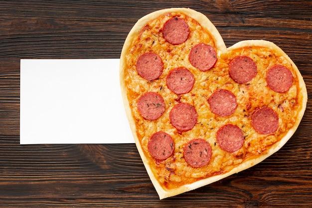 Schöne anordnung für valentinstag abendessen mit herzförmigen pizza und karte Kostenlose Fotos