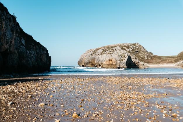 Schöne ansicht der ozeanwellen, die auf den felsen nahe dem strand unter einem blauen himmel zusammenstoßen Kostenlose Fotos