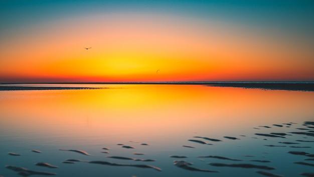 Schöne ansicht der reflexion der sonne im see gefangen in vrouwenpolder, niederlande Kostenlose Fotos