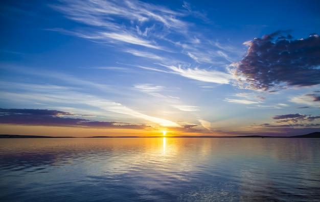 Schöne ansicht des meeres mit der sonne, die in einem blauen himmel im hintergrund scheint Kostenlose Fotos