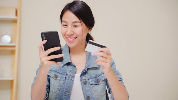 Schöne asiatin, die den smartphone kaufen online kaufen mit kreditkarte verwendet, während das zufällige sitzen auf schreibtisch im wohnzimmer zu hause sitzt. Kostenlose Fotos