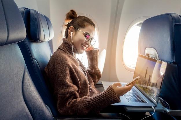 Schöne asiatische frau arbeitet mit laptop im flugzeug Premium Fotos