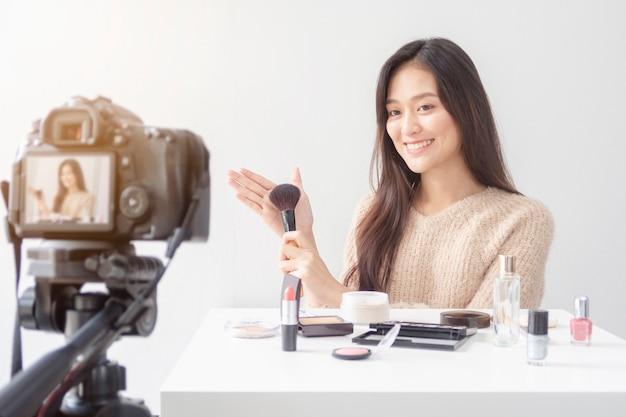 Schöne asiatische frau blogger zeigt, wie man kosmetik bildet und verwendet. Premium Fotos