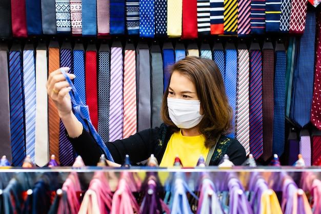 Schöne asiatische frau des mittelalters, die eine bunte krawatte im geschäft hält und wählt Premium Fotos