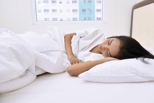 Schöne asiatische frau, die bequem mit schläft Premium Fotos