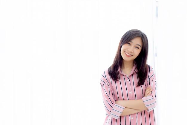 Schöne asiatische frau, die das fenster und lächeln während aufstehen steht Premium Fotos