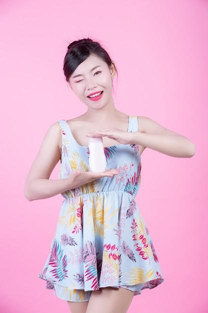 Schöne asiatische frau, die eine flasche des produktes auf einem rosafarbenen hintergrund anhält. Kostenlose Fotos