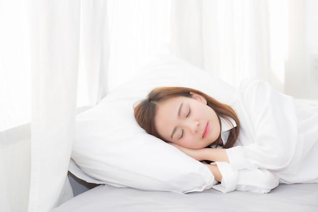 Schöne asiatische frau, die im bett liegend schläft Premium Fotos