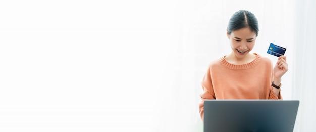 Schöne asiatische frau, die kreditkarte hält und digitale laptopeinkäufe online verwendet Premium Fotos