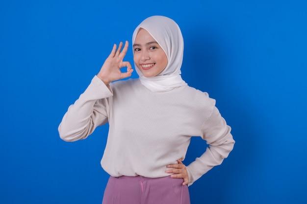 Schöne asiatische frau, die langen weißen t-shirt-lächelnausdruck mit ihrer hand verwendet Premium Fotos