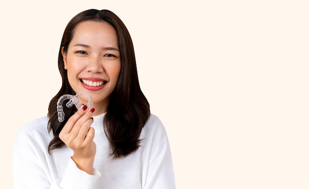 Schöne asiatische frau, die mit der hand hält den zahnmedizinischen ausrichtungshalter lächelt (unsichtbar) Premium Fotos
