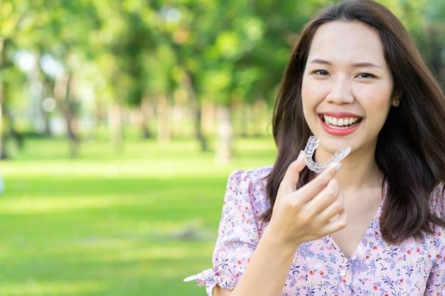 Schöne asiatische frau, die mit der hand hält zahnmedizinischen ausrichtungshalter naturpark am im freien lächelt Premium Fotos