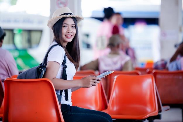 Schöne asiatische frau, die mit karte und tasche am busbahnhof lächelt Kostenlose Fotos