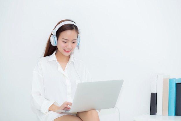Schöne asiatische frau entspannen sich mit abnutzungskopfhörer genießen hörende musik unter verwendung des laptops Premium Fotos