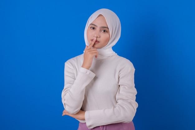 Schöne asiatische frau fröhlich unter verwendung des weißen t-shirt-lächelnausdrucks mit ihrer hand Premium Fotos