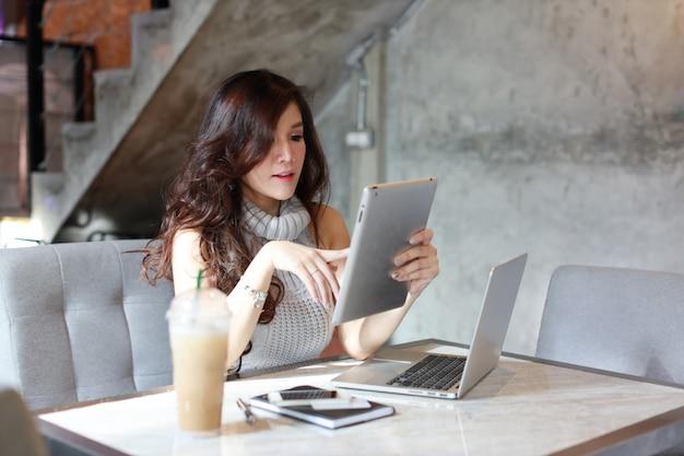 Schöne asiatische frau im freizeitkleidereinkaufen und in der online-zahlung auf tablette und computer Premium Fotos