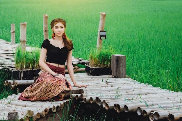Schöne asiatische frau im lokalen kleid, das auf bambusbrücke im reisfeld natürlich sitzt und genießen Premium Fotos