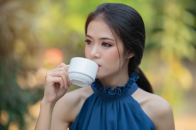 Schöne asiatische frau mit blauem kleid frischen morgen heißen kaffee zu trinken Premium Fotos