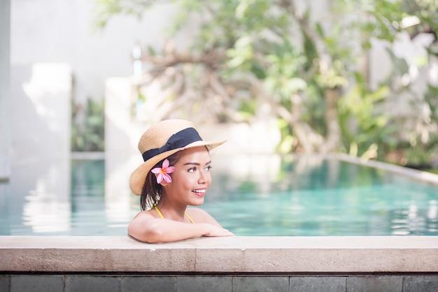 Schöne asiatische frau mit dem entspannenden hut Premium Fotos