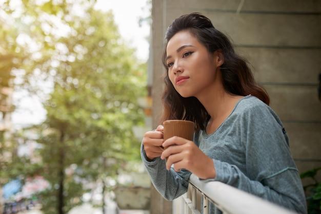 Schöne asiatische frau mit der tasse tee schauend aus ihrem balkon heraus Kostenlose Fotos