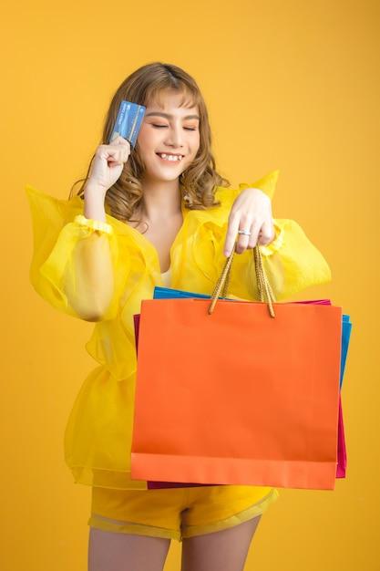 Schöne asiatische frau mit einkaufstasche und kreditkarte in der hand Kostenlose Fotos