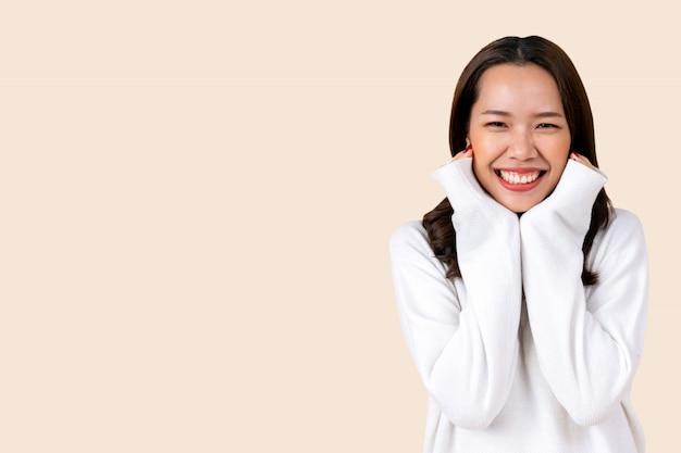 Schöne asiatische frau tragen warme lässige kleidung isoliert auf cremefarbenen hintergrund für die wintersaison für mode Premium Fotos