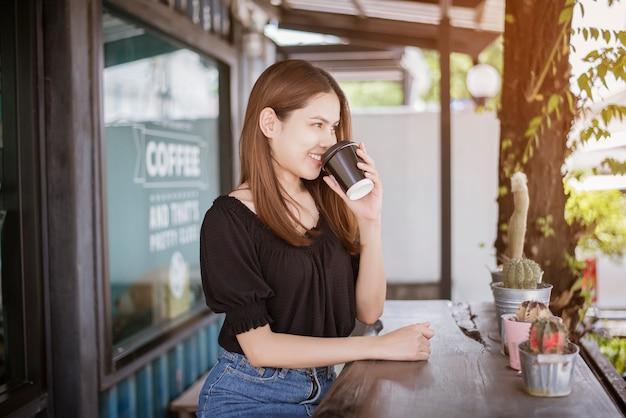 Schöne asiatische frau trinkt kaffee Premium Fotos