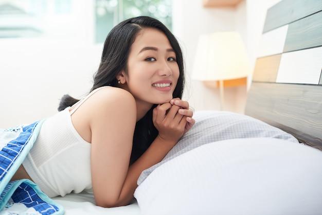Schöne asiatische frau unter decke im bett Kostenlose Fotos