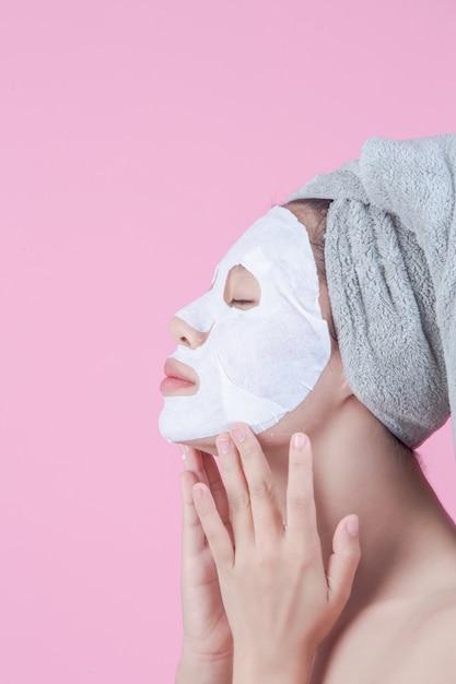 Schöne asiatische frauen benutzen gesichtsmaskengesicht auf blatt auf einem rosa hintergrund. Kostenlose Fotos