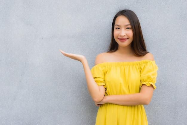 Schöne asiatische frauen des porträts lächeln glücklich mit konkretem hintergrund Kostenlose Fotos