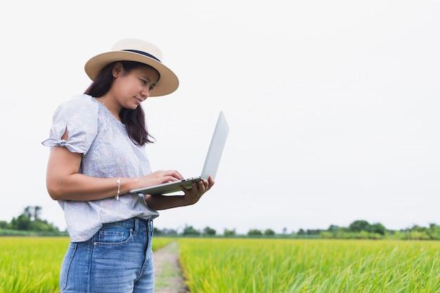 Schöne asiatische frauen, die auf dem reisgebiet stehen und unter verwendung eines laptops arbeiten, der zufällige kleidung trägt. Premium Fotos