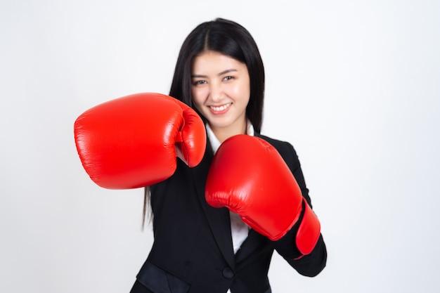 Schöne asiatische geschäftsfrau, die in der hand einen boxhandschuh und einen anzug trägt Kostenlose Fotos