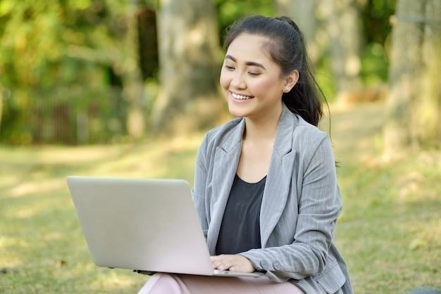 Schöne asiatische geschäftsfrau, die mit laptop arbeitet Premium Fotos