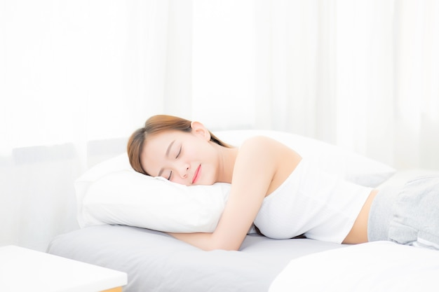 Schöne asiatische junge frau, die im bett mit kopf auf kissen liegend schläft. Premium Fotos
